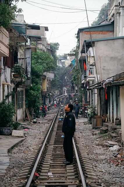 Man standing waiting on tracks, Hanoi (Vietnam)