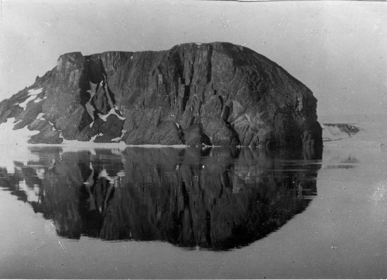 Скала и ее отражение в воде