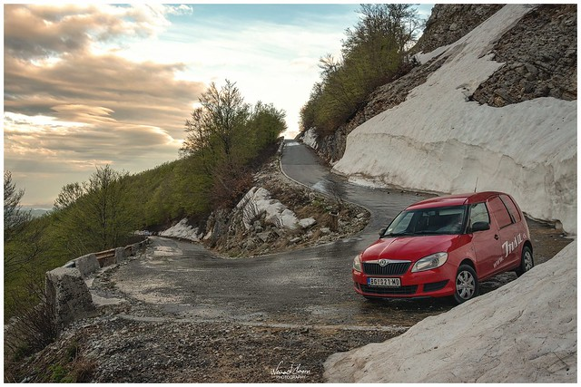 Lovcen Mountain road and red Skoda posing.