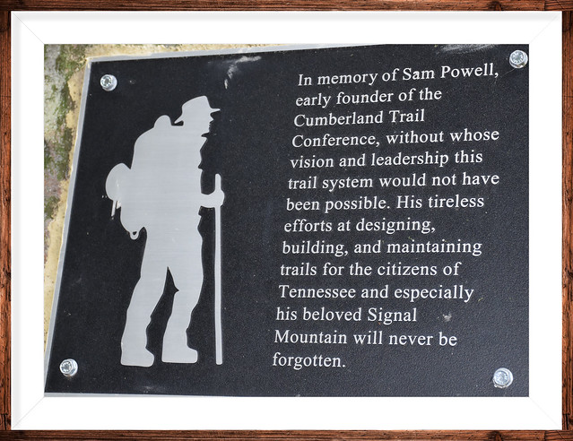 A plaque at the foundation of the swinging bridge