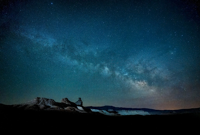 The Milky Way shines above the Mexican Hat rock formation lit up by passing car lights near Bluff, Utah