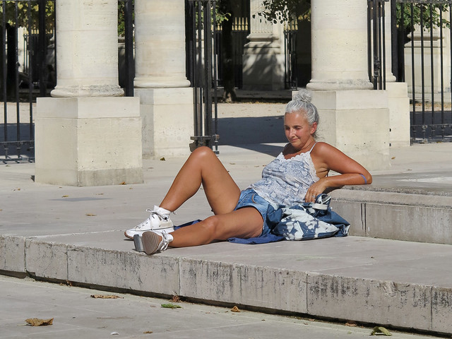 Woman in short jeans half-lying on the edge of a fountain
