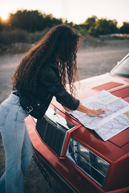Woman`s hand on a car map on vintage car outdoors.