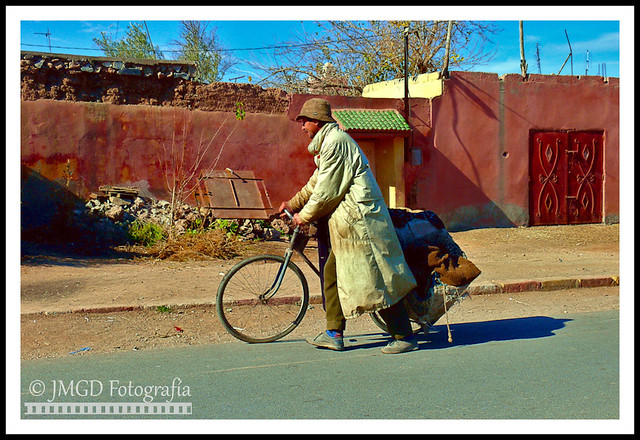 Man with trenchcoat and bicycle