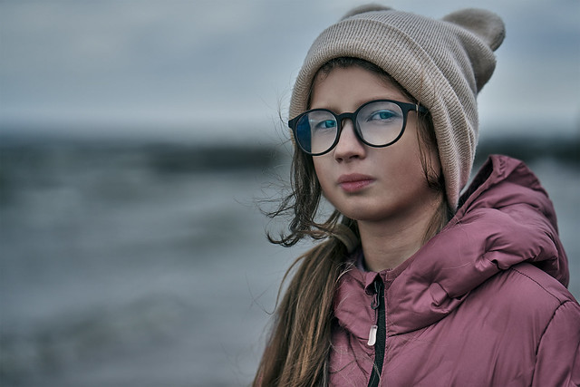 Portrait of a teenager girl on a walk on a cold windy cloudy autumn day.