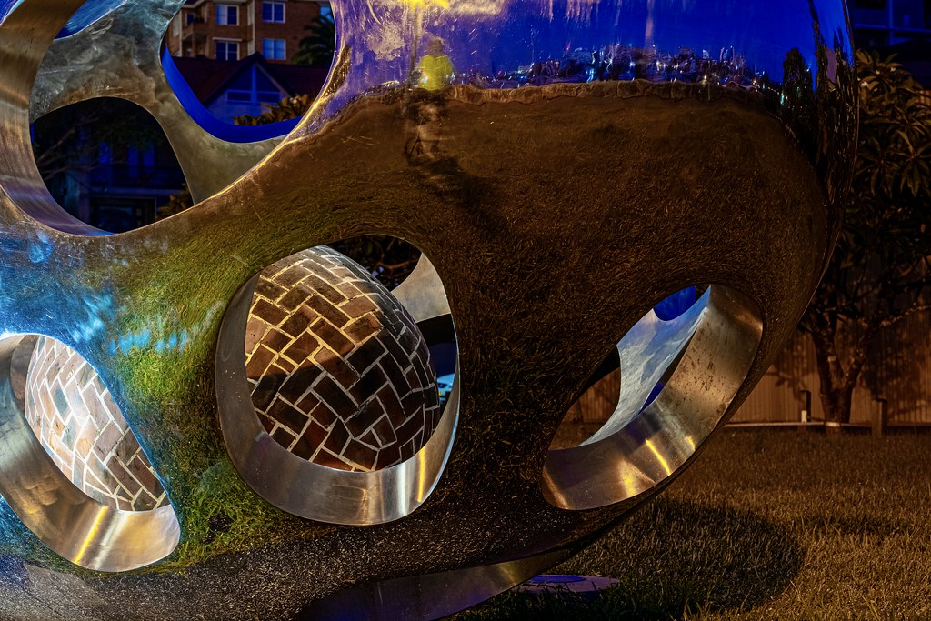 I really like public art, I had to get down on the dewy grass to grab this pre-dawn shot of a brick ball inside a metal ball at Sydney's Rushcutters Bay Park. . If you look in the reflection you'll see me in a flouro cycling shirt and Sydney's Potts Point