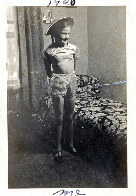 Girl in Dance Costume Posing by Bed, 1940