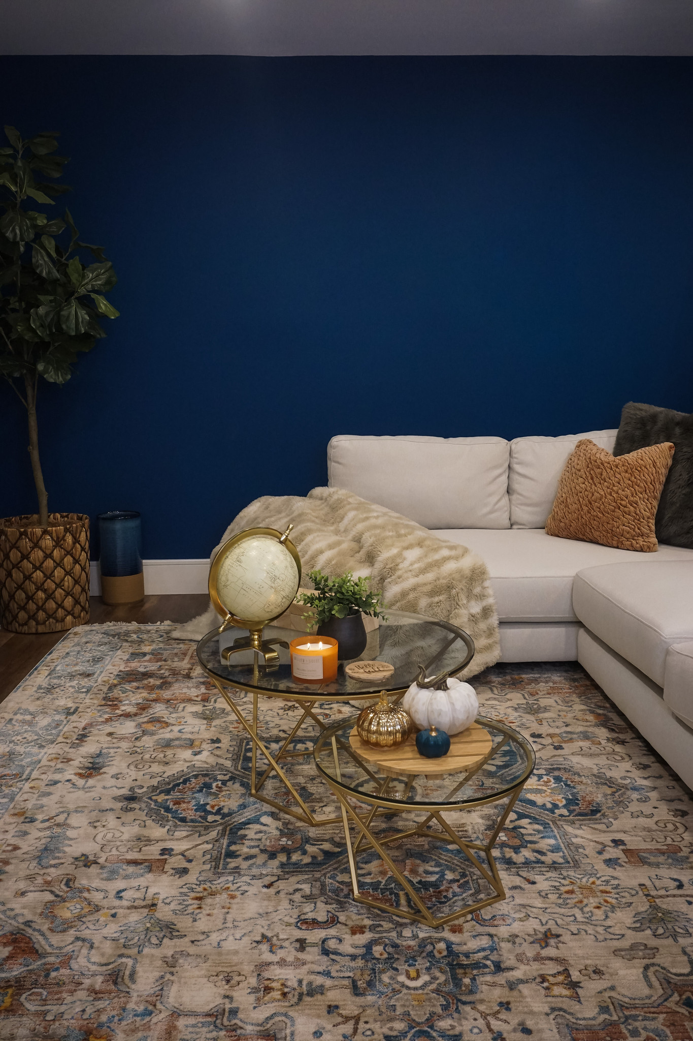 Living Room Fall Decor | Blue Walls | White Sectional Couch | Pumpkin Table Decor | Fall Candle on Coffee Table | How to Decorate Your Home for Fall