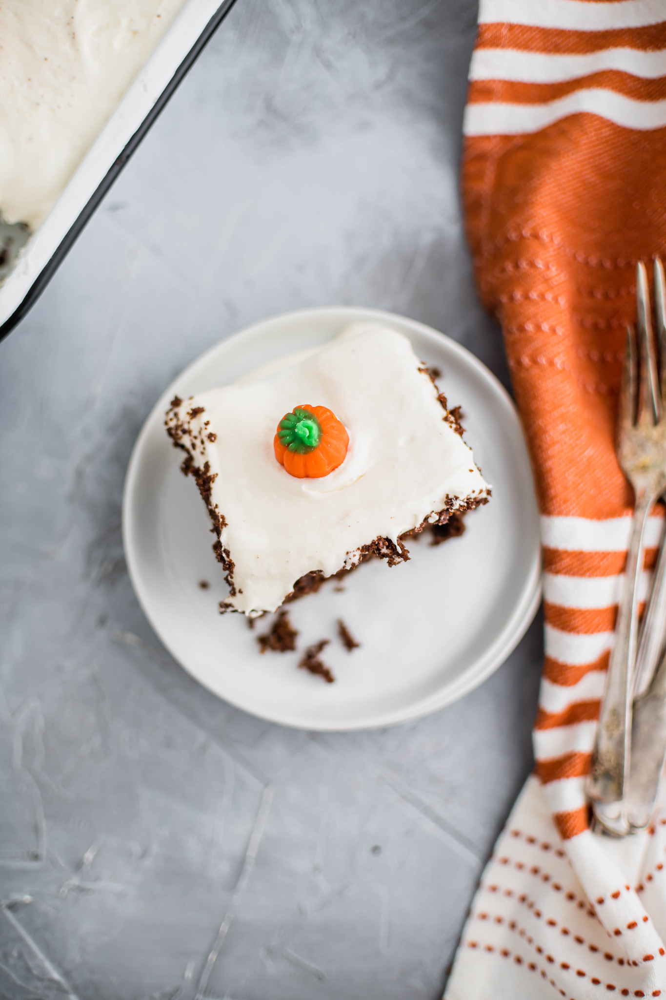 Slice of chocolate pumpkin cake on a small white round plate. Orange and cream striped cloth napkin and fork to the right of the plate.