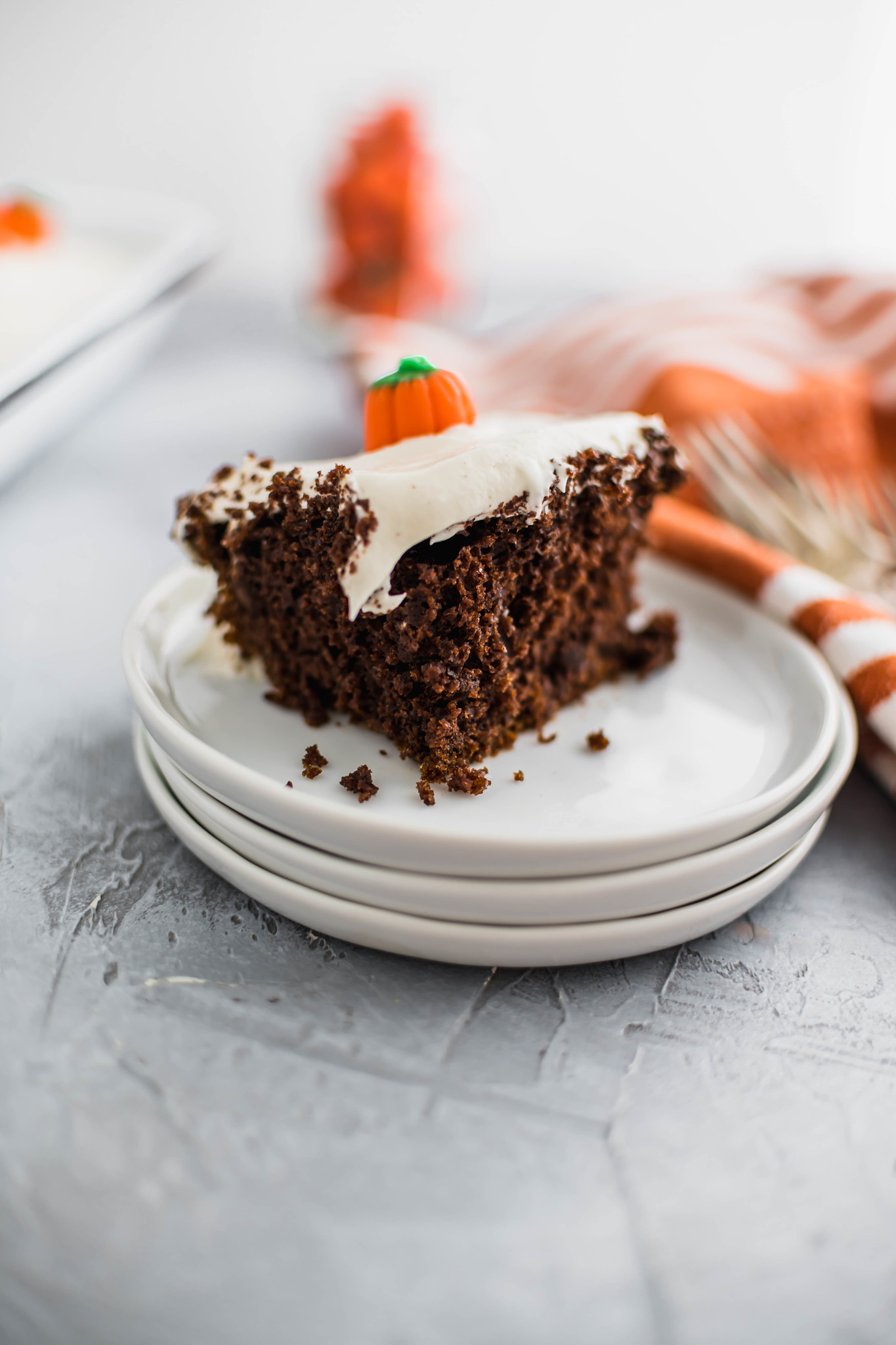 Picture of chocolate pumpkin cake showing cake texutre. Cake slice sits on small white round plate with forks and cloth napkin in the background.