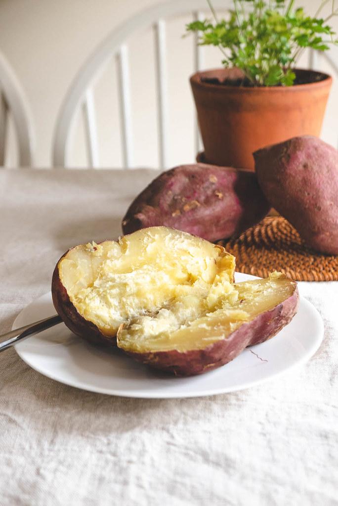 A Korean sweet potato cut open to show the yellow interior.