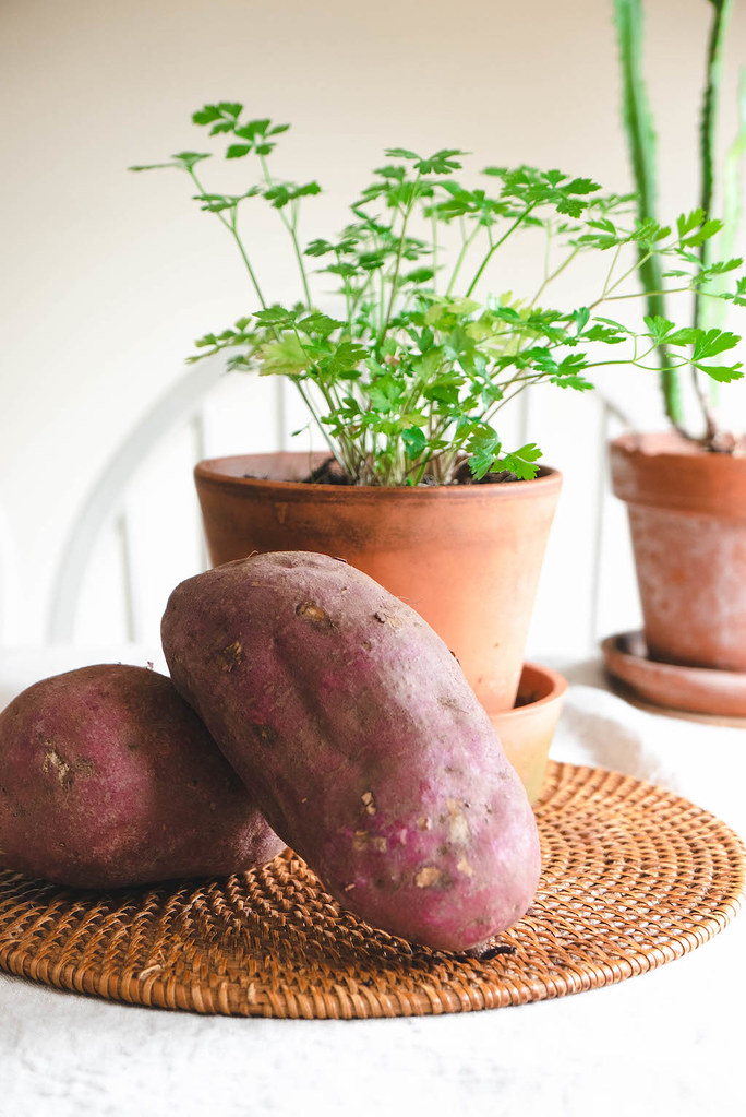 Large sweet potatoes next to green plants.