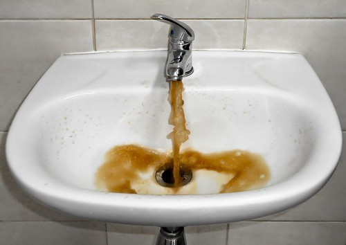 unclean water pouring from a bathroom faucet. From Linking Human Rights to Climate Change