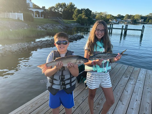 Photo of girl and boy on a dock, each holding a fish