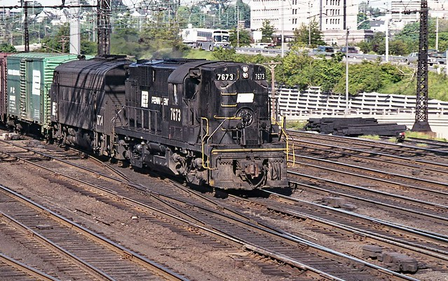 Penn Central ex New Haven Railroad ALCO RS-11 locomotive # 7673 along with EMD F7A locomotive # 1774 leads an eastbound manifest freight train on an express track near tower SS38 at Stamford, Connecticut, 1971