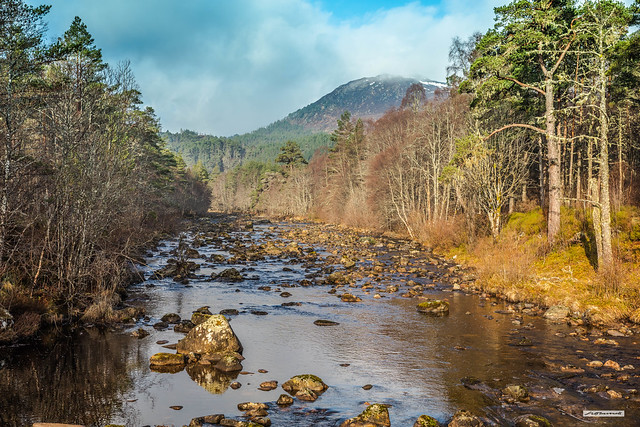 The risen sun at 07:23 shines on the river, rocks, banks, forest and mountains of Glen Affric as the cloud starts to fragment and the River Affric flows eastwards, near Dog Falls, Inverness-shire, Scotland.