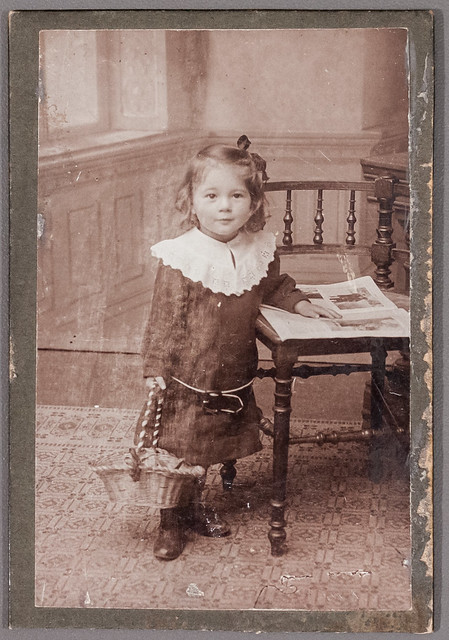 Portait of a child with a basket and a book