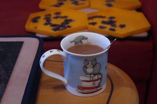 Englischer Tee mit Milch und Zucker (vor Bücherregal-Puzzleteilen)