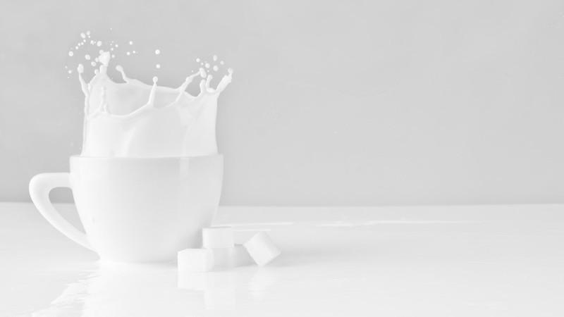 Sugar cube splashing in a cup of milk