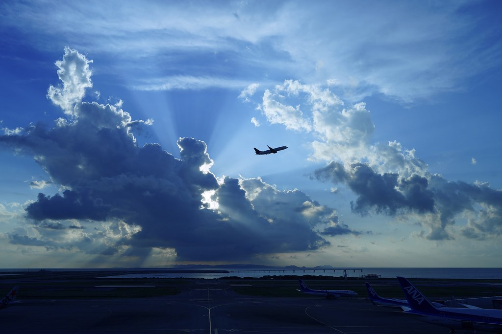 Cumulonimbus overflowing sun and airplane