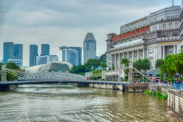 Cavenagh bridge spanning the Singapore river with Fullerton Hotel and Esplanade - Theaters by the Bay