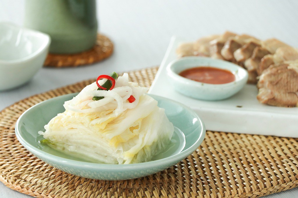 Baek kimchi sitting next to boiled or steamed pork belly.