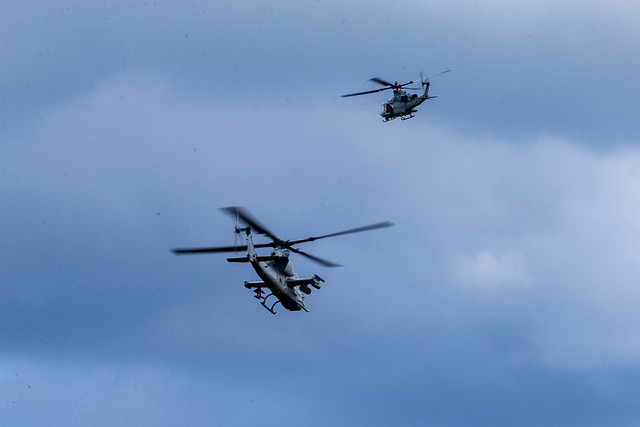 A UH-1Y Venom and an AH-1Z Viper twin-engine attack helicopter leave a forward refueling point