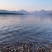 Smokey hazy view of Lake McDonald at sunset in Glacier National Park. Pebbles in foreground in selective focus