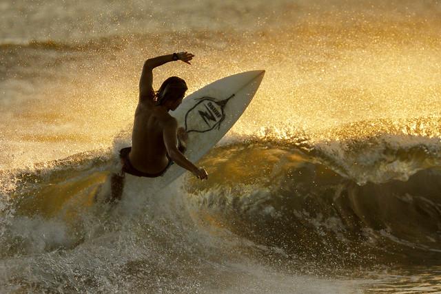 Surfer illuminated by the setting sun