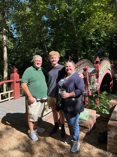Brendan Wommack '25 poses for a photo by the Crim Dell bridge with his parents during Family Weekend.