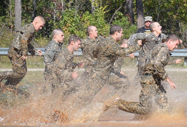 Soldiers running through muddy water