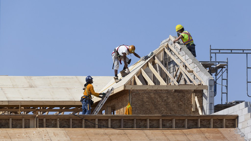 Construction workers completing a house roof