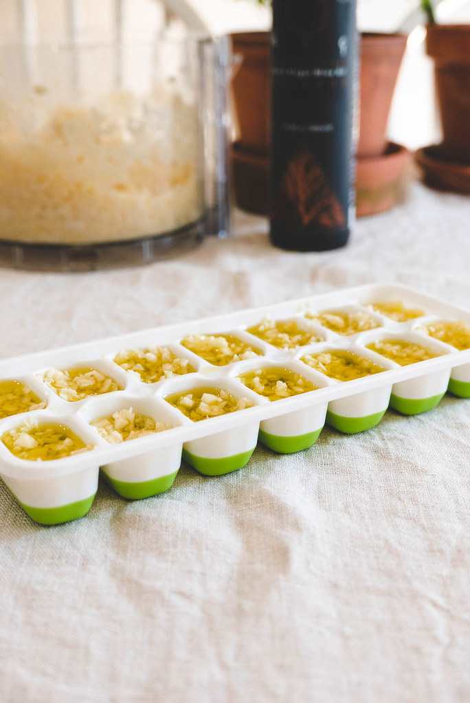 An ice tray filled with minced cloves and olive oil.