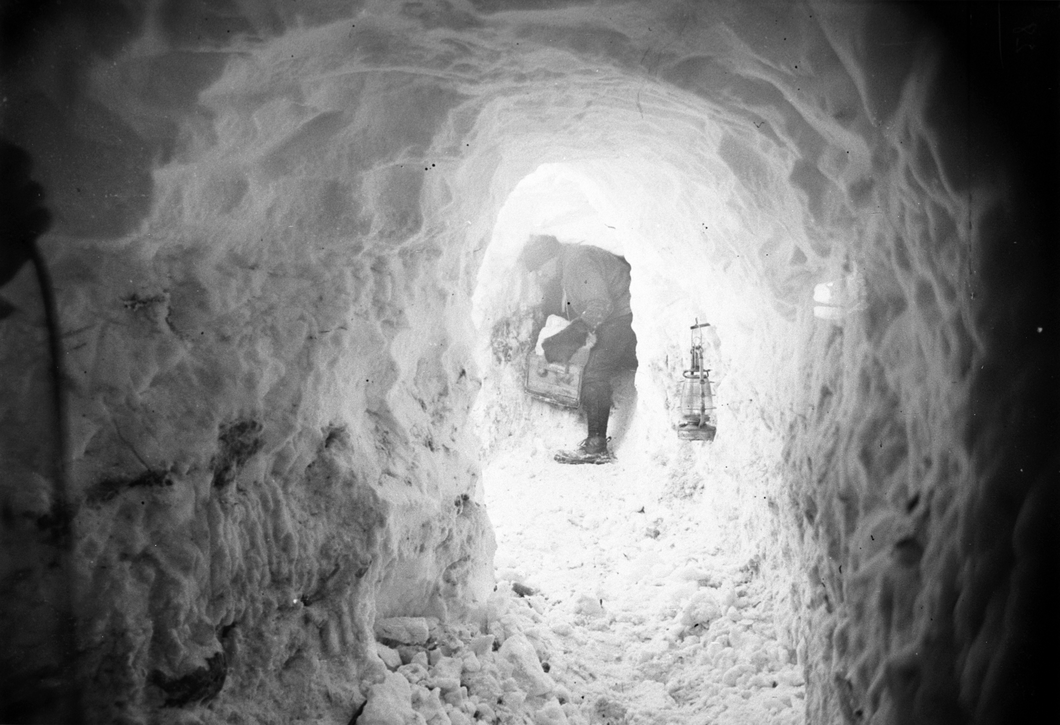 Xavier Mertz Bringing in a box of Ice through the Catacombs, Antarctica,  1912, by Frank Hurley