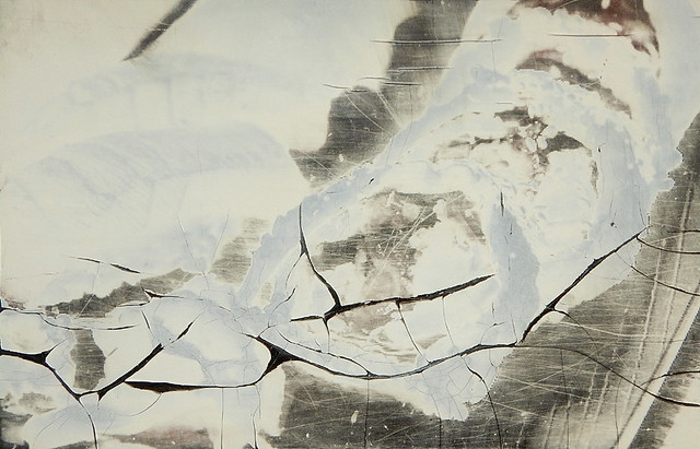 Abstract of cracked white & grey poster on a window
