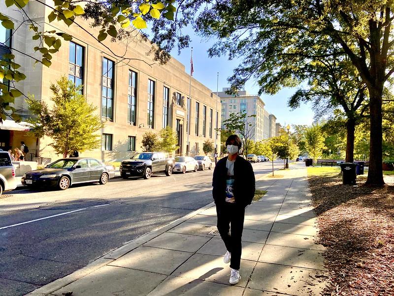 A man wearing a face mask walks down the sidewalk