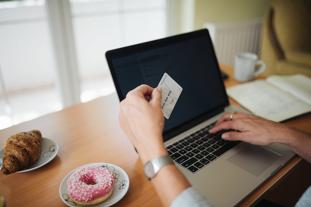 Middle-aged woman holding credit card and typing on laptop at home. Arms closeup.