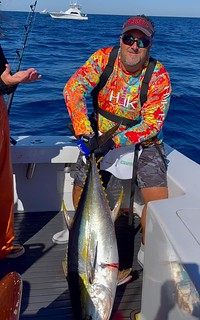 Photo of man on a boat holding a yellowfin tuna