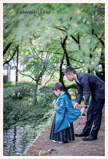 七五三 神社の池の鯉にえさをあげる男の子
