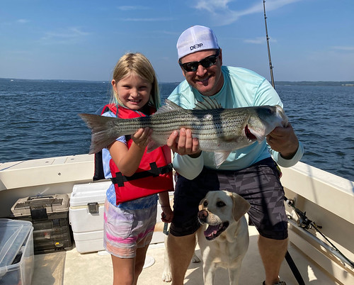 Photo of young girl with her father, and a dog, holding a striped bass on a boat.