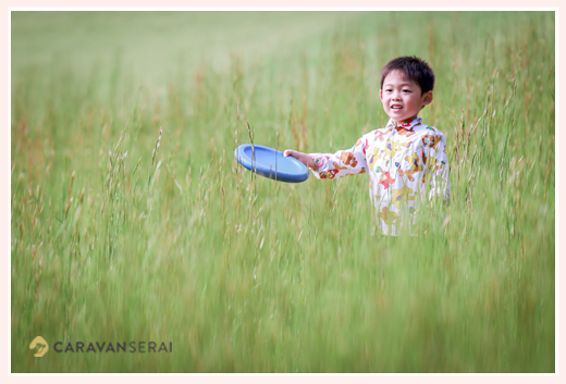 草原のような草むら その中で遊ぶ男の子