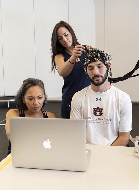 Melissa Pangelinan and Mary Grayson Nix work with graduate student Cole Burton.
