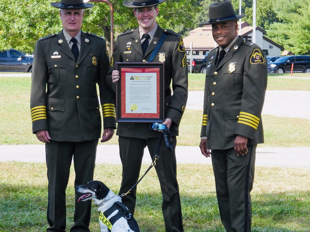 Photo of three police officers and a dog