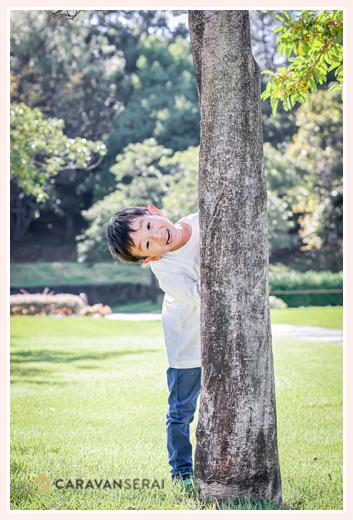 木陰から顔を出す男の子