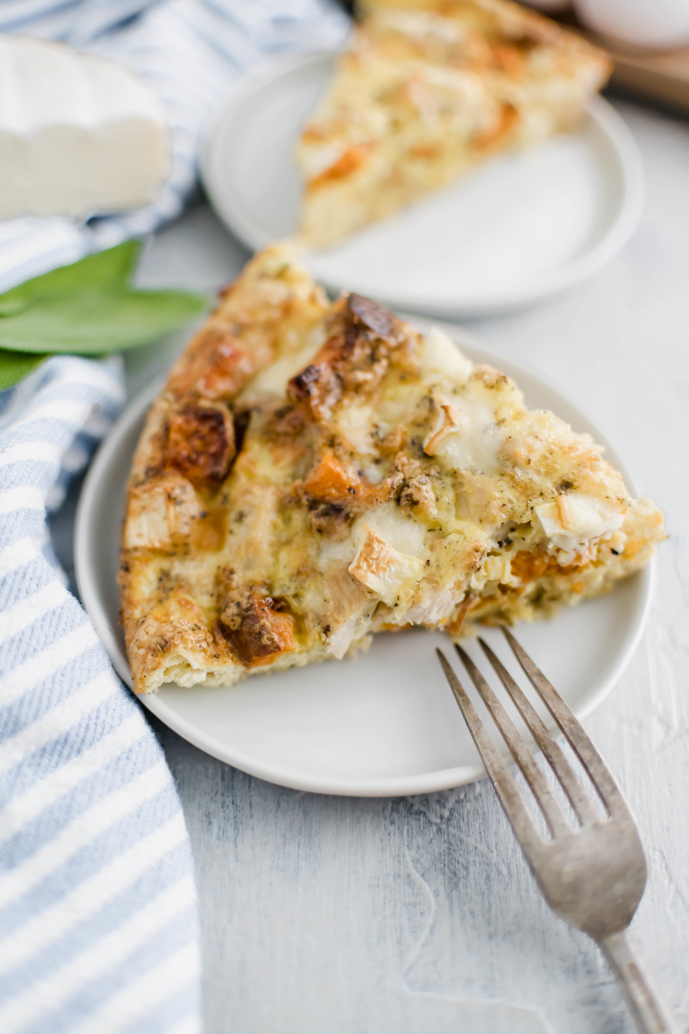 Close up of turkey frittata on a small white plate with a fork leaning on the plate.