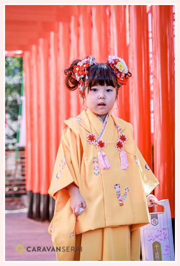 七五三 3歳の女の子 オレンジの着物が衣装 赤い鳥居の下で