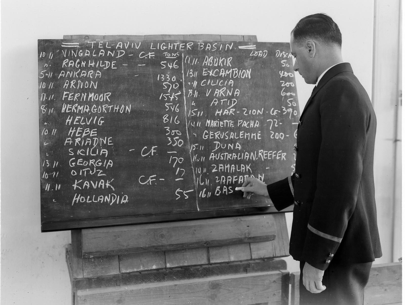 17. 1938. Клерк в порту Тель-Авива пишет на доске