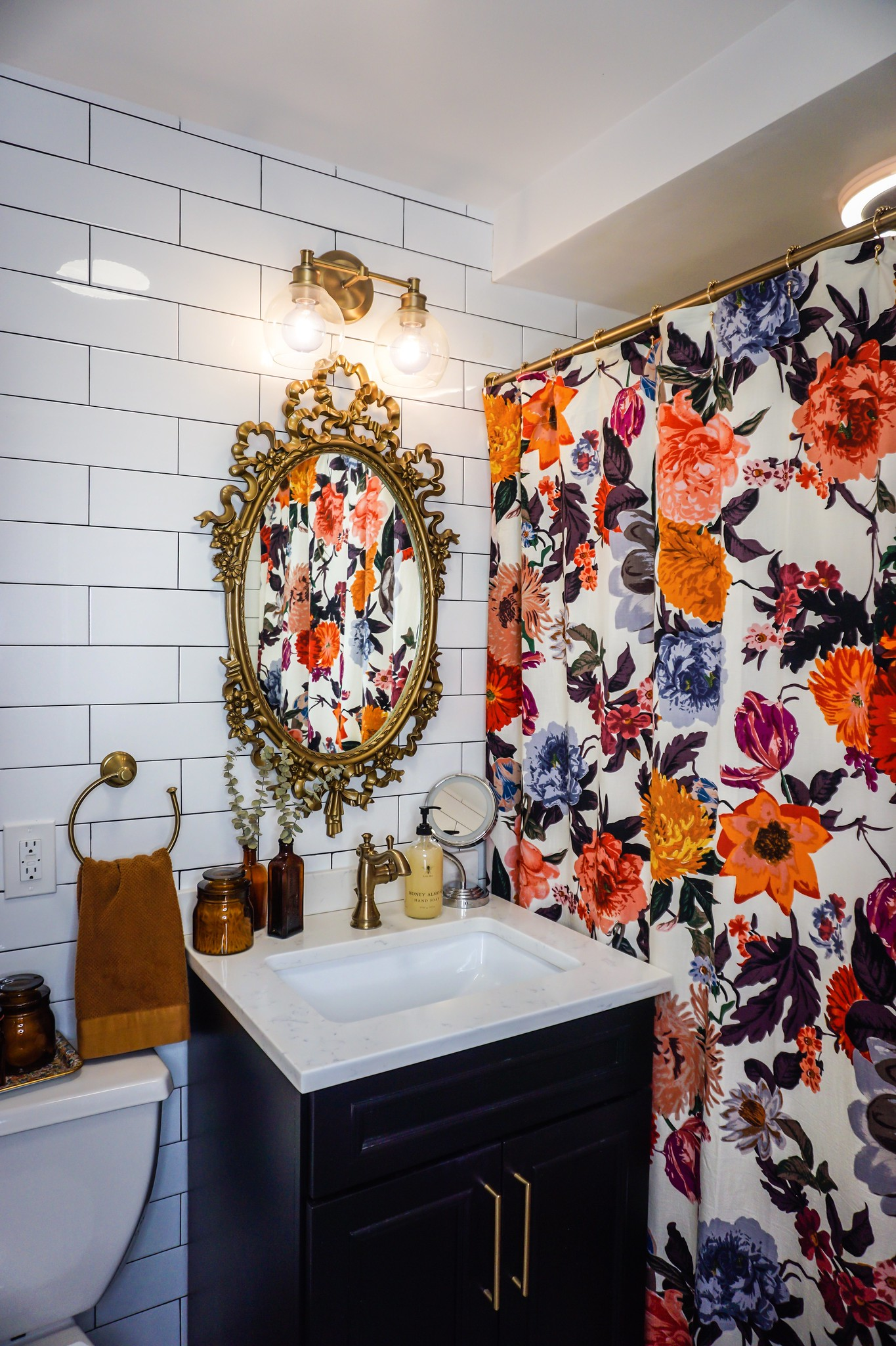Burnt Orange Glass Canisters in Bathroom | Gold Vintage Mirror | Floral Shower Curtain | Small Bathroom Inspiration