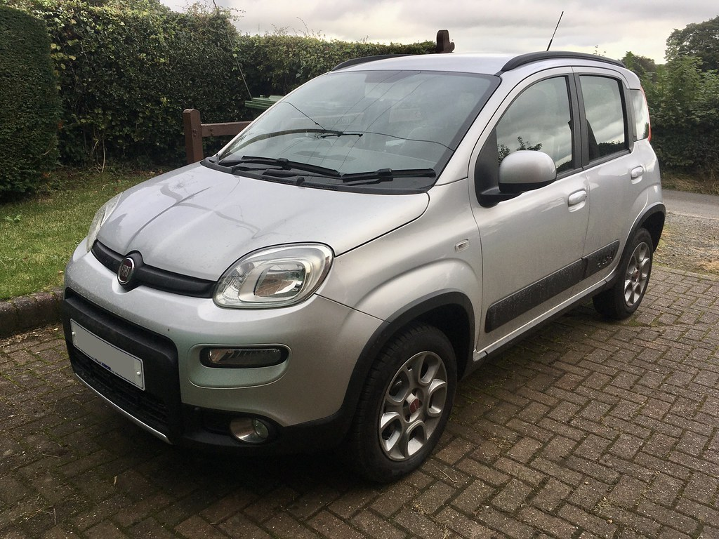 A photo of a small silver Fiat Panda 4x4 on a brick-paved driveway with green hedges in the background