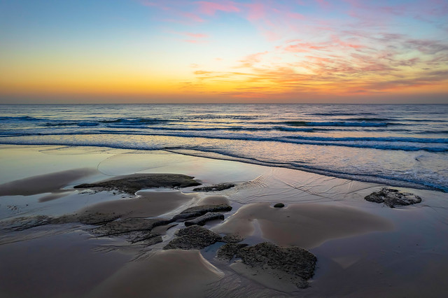 Aerial sunrise seascape with high cloud and gentle surf